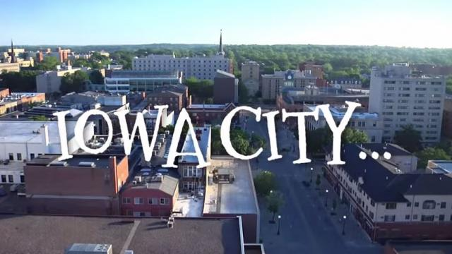 "Iowa City skyline during the day with the words ""Iowa City"" over it."