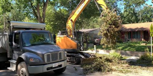 Crews are shown cleaning storm debris from the curb.