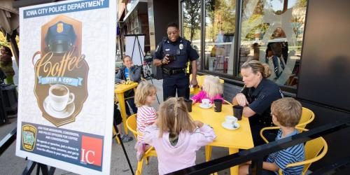 Iowa City police officers talking to kids at a Coffee with a Cop event.
