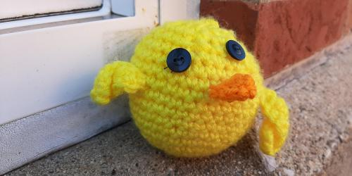 A yellow, crochet duck is shown.