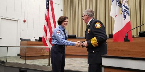 After being sworn in as an Iowa City firefighter, Maria Koeppel, left, shakes hands with Iowa City Fire chief John Grier, right.  Caption On Friday, Nov. 15, 2019, the Iowa City Fire Department welcomed a new firefighter Maria Koeppel during a badge pinni