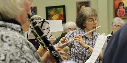 A group of women play instruments in a band.