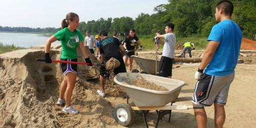 A group of young people work to build a natural playscape at Terry Trueblood Recreation Area.