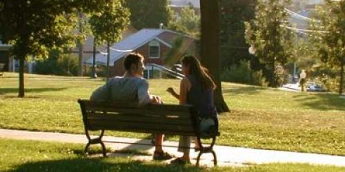 A man and woman sit on a park bench talking on a summer day.