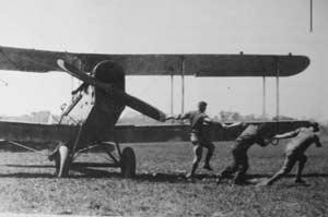 Three men starting an airmail plane.