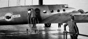 A man boards a Boeing 247 in the new United Hangar as another man looks on in 1934.