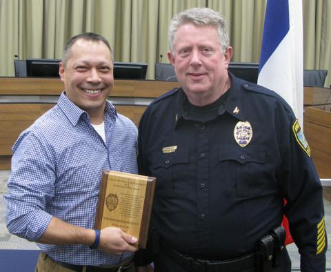 Officer Dave Gonzalez receives the 2015 Iowa City Police Department Officer of the Year award from ICPD Chief Sam Hargadine.
