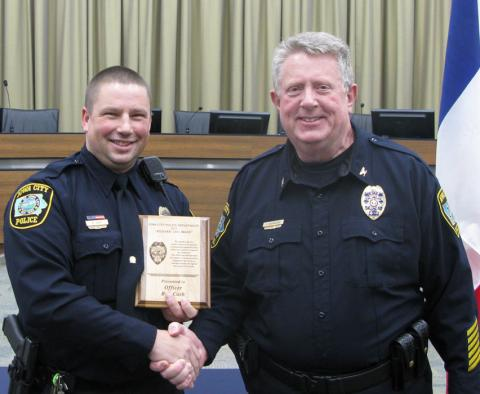 """Officer Rob Cash receives the 2015 Iowa City Police Department Richard """"Dick"""" Lee award from ICPD Chief Sam Hargadine."""