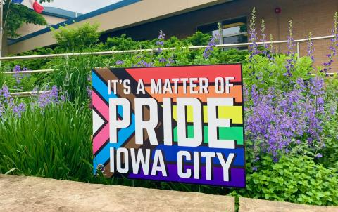 A sign with a rainbow background and the phrase 'It's a matter of Pride Iowa City' is shown.