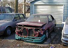 An inoperable vehicle parked in a driveway.
