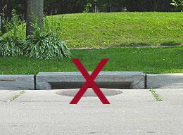 A self-cleaning storm drain on a street curb with a red x mark over it because it is not adoptable.