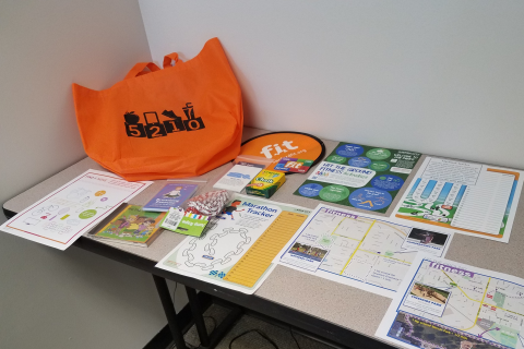 A bag with items such as a frisbee, chalk, jump rope, maps of parks, and more is shown.