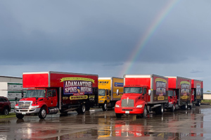 Picture of Adamantine Spine Moving company's fleet of moving trucks with rainbow in background