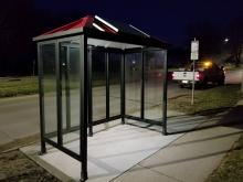 A bus stop lit at night by a solar panel.