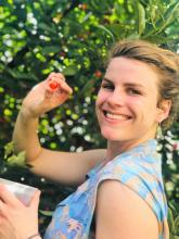 Giselle Bruskewitz holds a cherry tomato and smiles at the camera