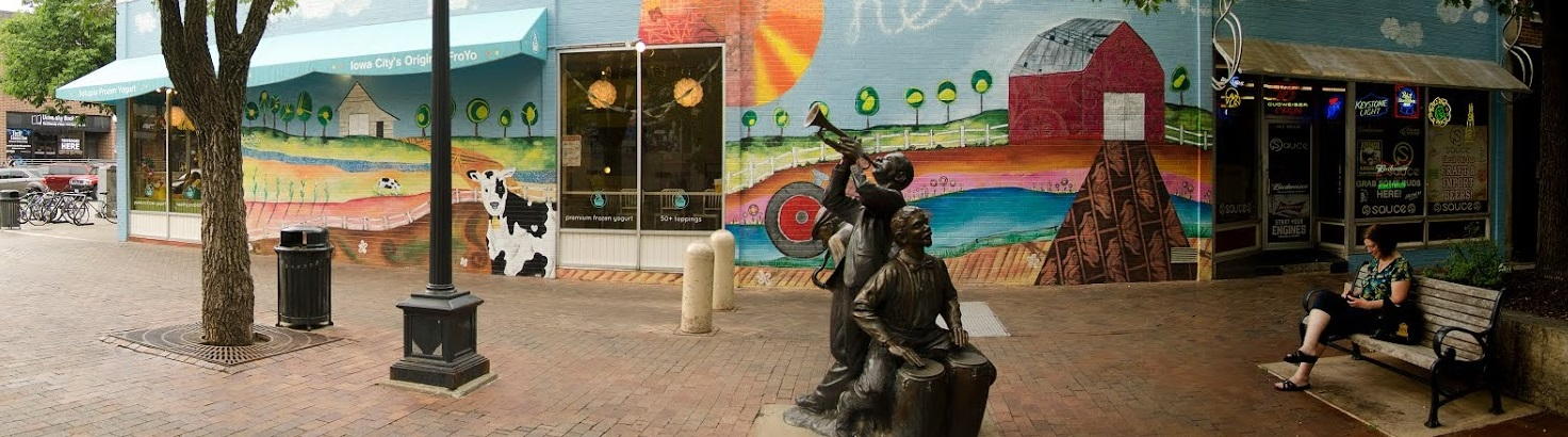 A mural and a statue are shown in Downtown Iowa City.